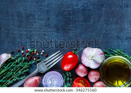 Fresh herbs, organic vegetables, olive oil and spices for cooking on dark vintage background. Healthy food. Vegetarian eating. Top view. Dark rustic background layout with free text space - stock photo