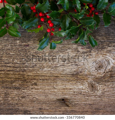 Fresh Holly branch with green leaves and red berries on wooden background - stock photo