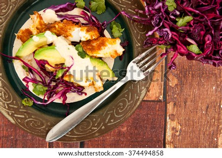 Fresh, home made fish tacos served with avocado and a red cabbage side salad. Presented on a rustic wooden table. - stock photo