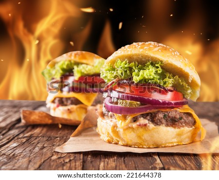 Fresh home-made hamburgers served on wooden planks. Fire flames around - stock photo