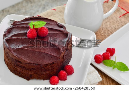 Fresh home made sticky chocolate cake with raspberries - stock photo