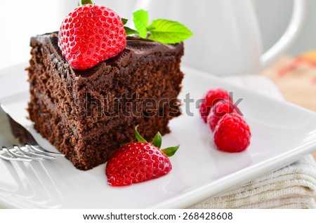 Fresh home made sticky chocolate cake with strawberries and raspberries - stock photo