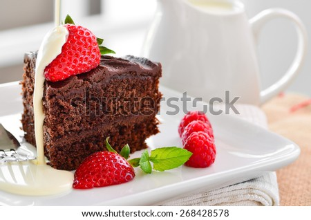 Fresh home made sticky chocolate cake with strawberries and raspberries with a jug of fresh pouring cream in the background.