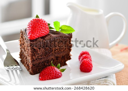 Fresh home made sticky chocolate cake with strawberries and raspberries with a jug of fresh pouring cream - stock photo