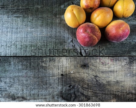 Fresh homegrown apricots on vintage weathering wooden table - stock photo