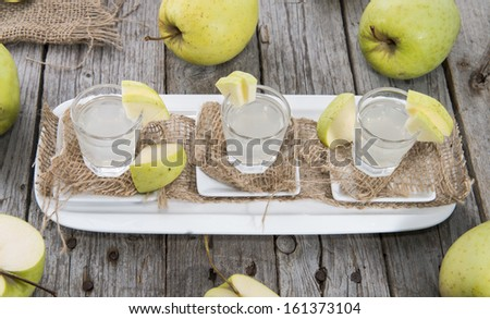 Fresh homemade Apple Liqueur with some fruits - stock photo