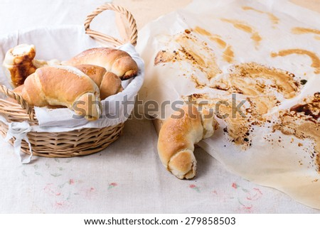 Fresh homemade baked bagels in basket and on baking paper over light gray tablecloth