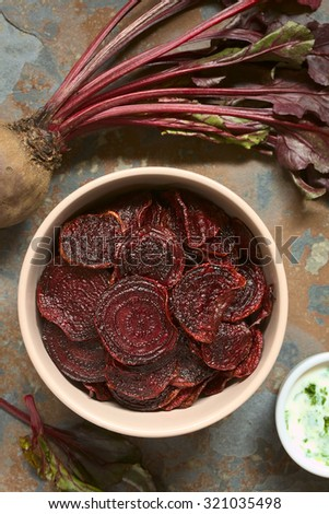 Fresh homemade beetroot chips in bowl, yogurt dip on the side, photographed overhead on slate with natural light (Selective Focus, Focus on the chips on the top) - stock photo
