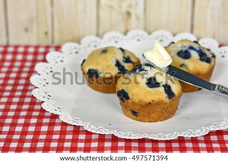 fresh homemade blueberry muffins on white plate with checkered tablecloth