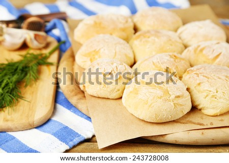 Fresh homemade bread buns from yeast dough and fresh garlic, dill  on cutting board, on color napkin background - stock photo