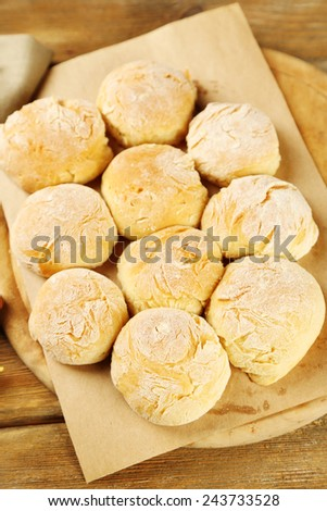 Fresh homemade bread buns from yeast dough on wooden board, on color napkin background - stock photo