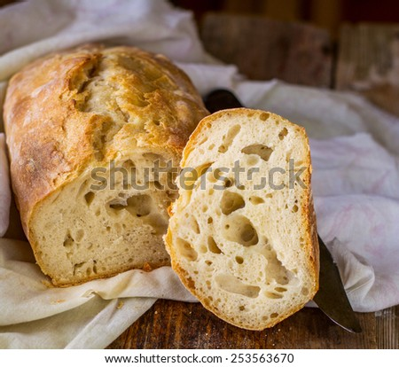 Fresh homemade bread in a cotton cloth on a wooden background. selective Focus - stock photo