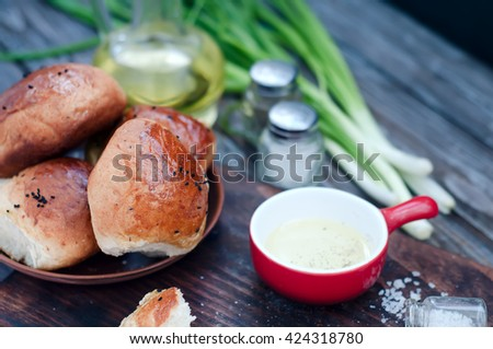Fresh homemade bread rolls with sesam seed on table - stock photo
