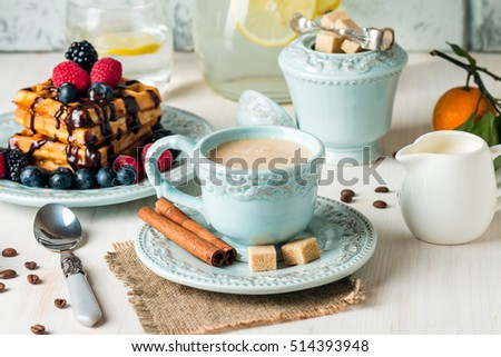 Fresh homemade brussels waffles with berries, chocolate and coffee for breakfast on white wooden background