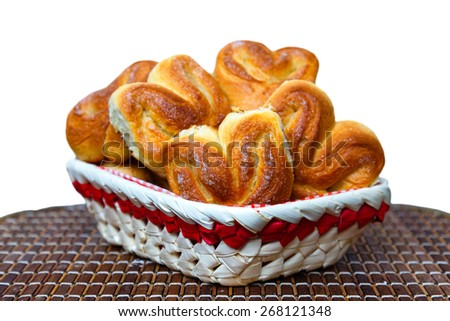 Fresh homemade buns in a basket on a bamboo tray on a white background - stock photo