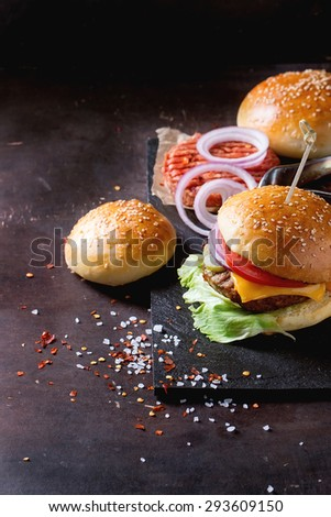 Fresh homemade burger on black slate and raw cutlet and sliced onion, served with sea salt and pepper over dark background - stock photo