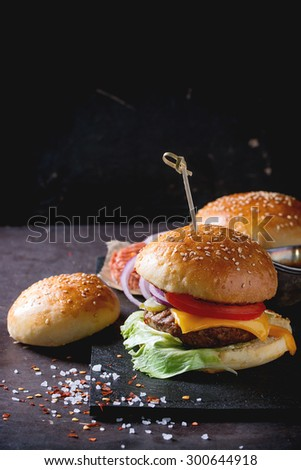 Fresh homemade burger on black slate and raw cutlet and sliced onion, served with sea salt and pepper over dark background. - stock photo