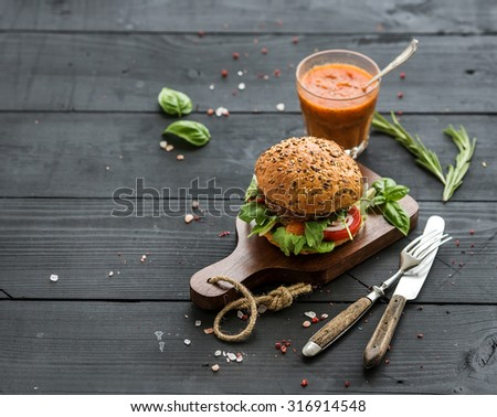 Fresh homemade burger on dark serving board with spicy tomato sauce, sea salt and herbs over dark wooden background, copy space - stock photo