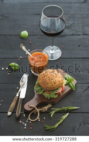 Fresh homemade burger on dark serving board with spicy tomato sauce, sea salt, herbs and glass of red wine over black wooden background. Selective focus - stock photo
