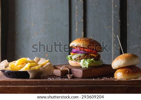 Fresh homemade burger on little cutting board with grilled potatoes, served with ketchup sauce and sea salt over wooden table with gray wooden background. Dark rustic style - stock photo