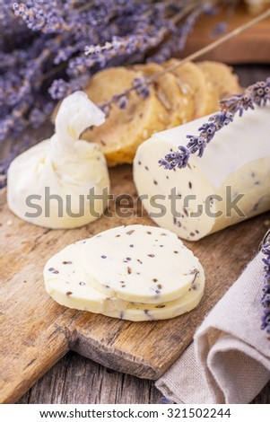 Fresh homemade butter with lavender flowers in a rolled parchment on a wooden cutting board with lavender flowers. The concept of natural organic food home. selective Focus - stock photo