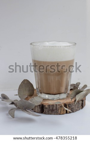Fresh homemade cappuccino in glass on white background with wood and eucalyptus