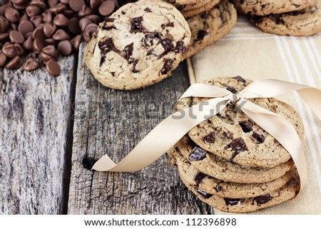 Fresh homemade chocolate chip cookies with chocolate chips and more cookies in the background. Shallow depth of field. - stock photo