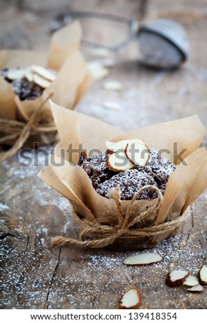 Fresh homemade chocolate muffins with sliced almonds - stock photo
