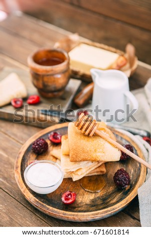 Fresh homemade crepes with honey and berries over rustic background