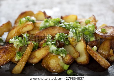 Fresh homemade crispy fried potato wedges with green garlic