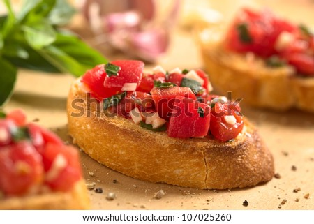 Fresh homemade crispy Italian antipasto called Bruschetta topped with tomato, garlic and basil on wooden board (Selective Focus, Focus on the front of the middle bruschetta) - stock photo