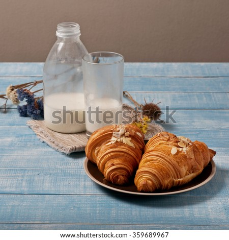 Fresh homemade croissants with almond chips and milk on a wooden table in the rustic kitchen close-up. Top view with copy space. Square frame