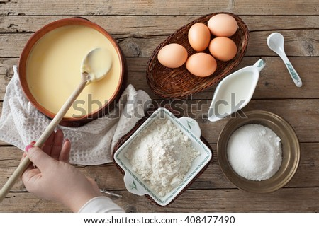 Fresh homemade custard cream and some of the ingredients necessary for its preparation: eggs, milk, flour and sugar.