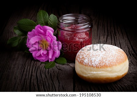Fresh homemade donut covered by sugar powder frosting, wild rose flower and jar of red fruit jam. Sweets composition taken on rustic table. - stock photo