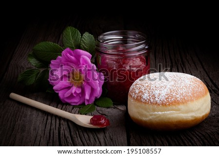 Fresh homemade donut covered by sugar powder frosting, wild rose flower and jar of red fruit jam. Sweets composition taken on rustic table.
