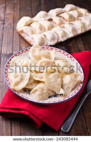 Fresh homemade dumplings on plate on wooden background. - stock photo