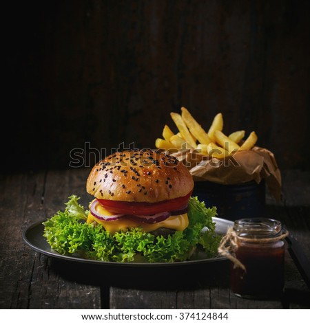 Fresh homemade hamburger with black sesame seeds in old metal plate with French fries, served with ketchup sauce in glass jar over wooden table with dark background. Dark rustic style. Square image