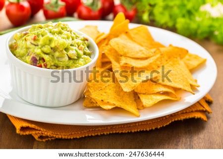 fresh homemade hot guacamole with tortilla chips - stock photo