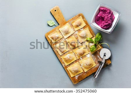 fresh homemade Italian ravioli with beetroot and ricotta cheese on a gray background - stock photo