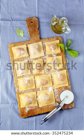 fresh homemade Italian ravioli with beetroot and ricotta cheese on blue striped tablecloth - stock photo