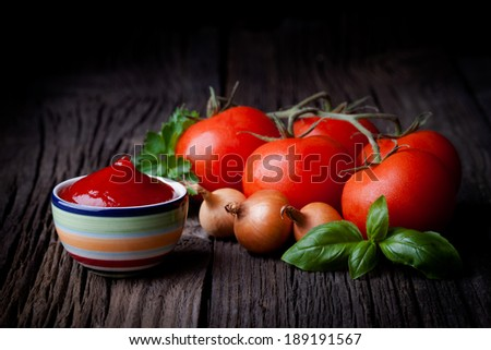 Fresh homemade ketchup and ingredients composition. Vegetables and sauce photography taken on rustic old table.