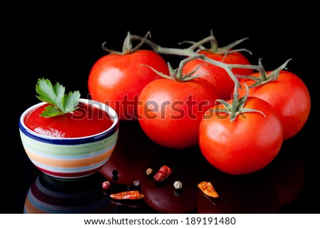 Fresh homemade ketchup and tomatoes composition. Vegetables photography taken on black surface.