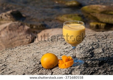 Fresh homemade mango milkshake in a glass served outside on a stone at the beach. - stock photo
