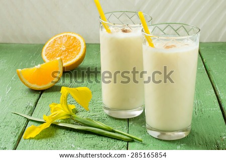 Fresh homemade milkshake with ice cream, orange juice and nutmeg in a glass with cocktail straws, slices of orange, iris flower on a green wooden table. Selective focus
