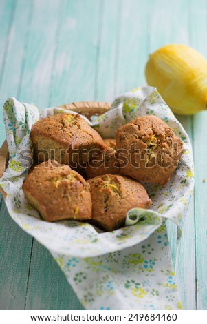 Fresh homemade muffins with lemon and poppy seeds  on painted wooden planks. Selective focus.