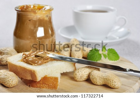 Fresh homemade peanut butter sandwich and peanuts on wooden cutting board - stock photo