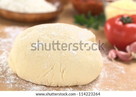 Fresh homemade pizza dough on floured wooden board with pizza ingredients (flour, tomato, grated cheese and herbs) in the back (Selective Focus, Focus one third into the pizza dough)