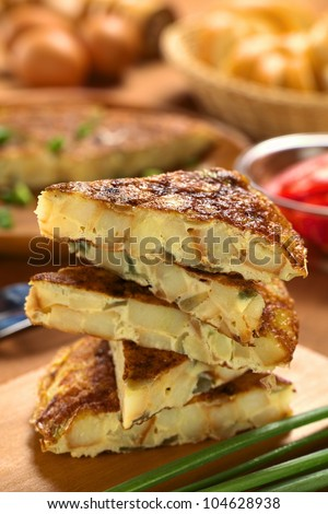 Fresh homemade Spanish tortilla (omelette with potatoes and onions) slices piled on wooden cutting board (Selective Focus, Focus on the front upper edge of the upper tortilla slice) - stock photo