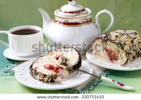 Fresh homemade sponge roll with cream cheese and cherry jam, decorated with chocolate icing and almond petals, cup of tea and teapot. Selective focus - stock photo