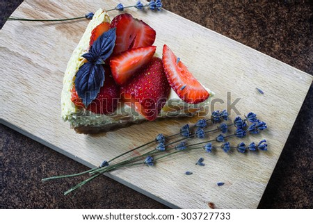 Fresh homemade strawberry cheesecake with basil and lavender on wooden background (Selective Focus)